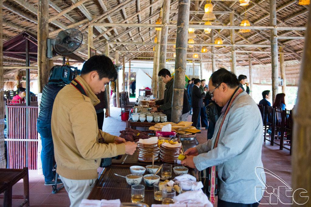 Các thành viên đoàn khảo sát thưởng thức đặc sản địa phương tại làng Yên Đức